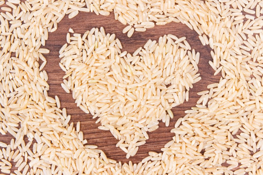 Heart shaped brown rice on rustic board