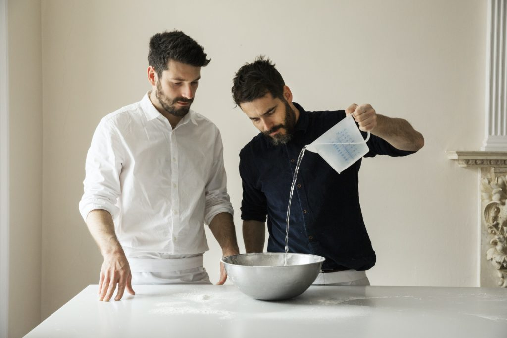 Two bakers preparing bread dough, pouring water from a measuring jug into a metal mixing bowl.