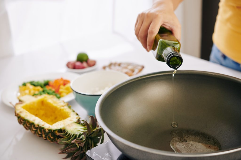 Woman pouring oil in frying pan