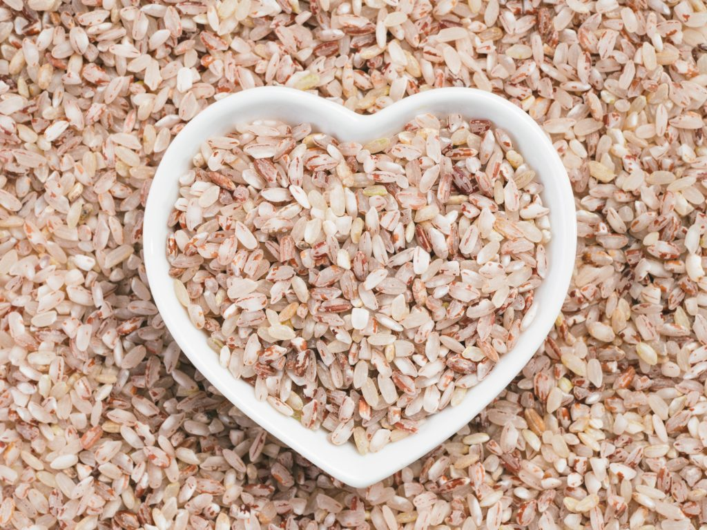 Red rice in heart-shaped bowl on rice background