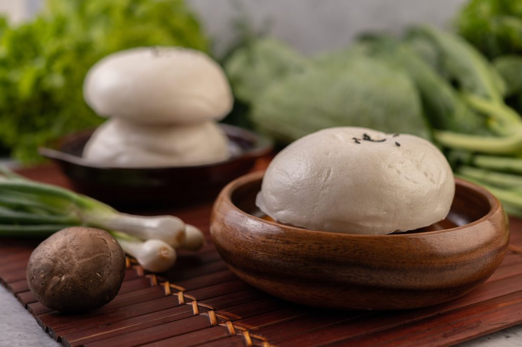 Steamed buns in a wooden dish on a wooden grill.